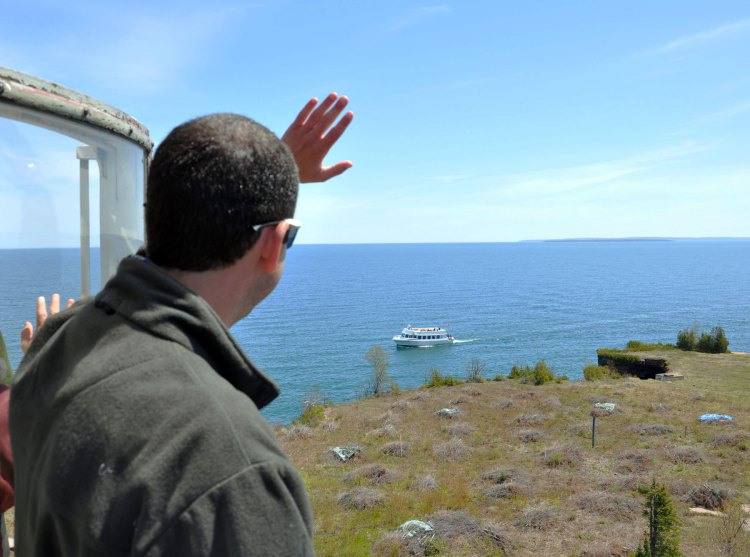 Josh Sweet waving to the cruise boat from the top of the tower at Devils Island