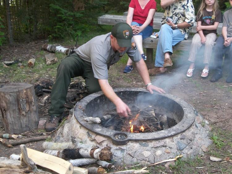 Dan building a fire for his evening program at Stockton Island