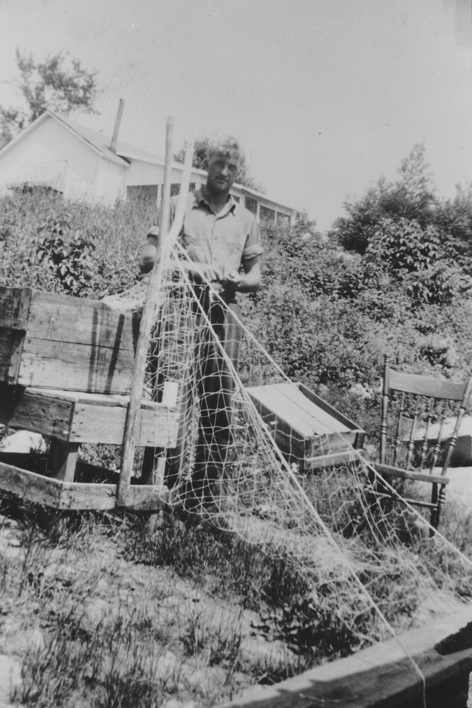 Julian Nelson works on a gill net in front of his cabin