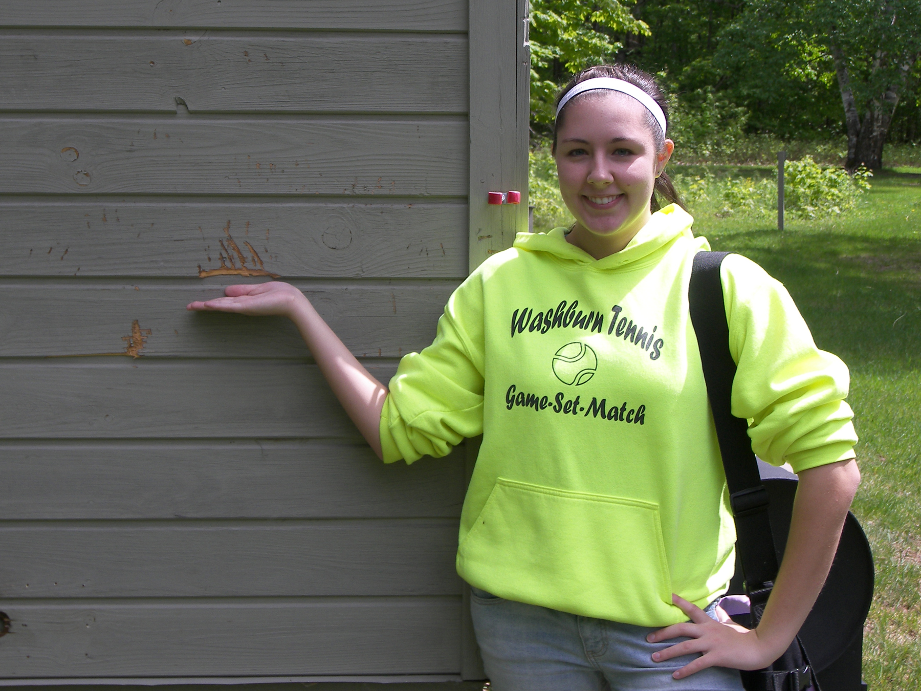 Jennie shows off claw marks from a bear on the Oak Island ranger cabin
