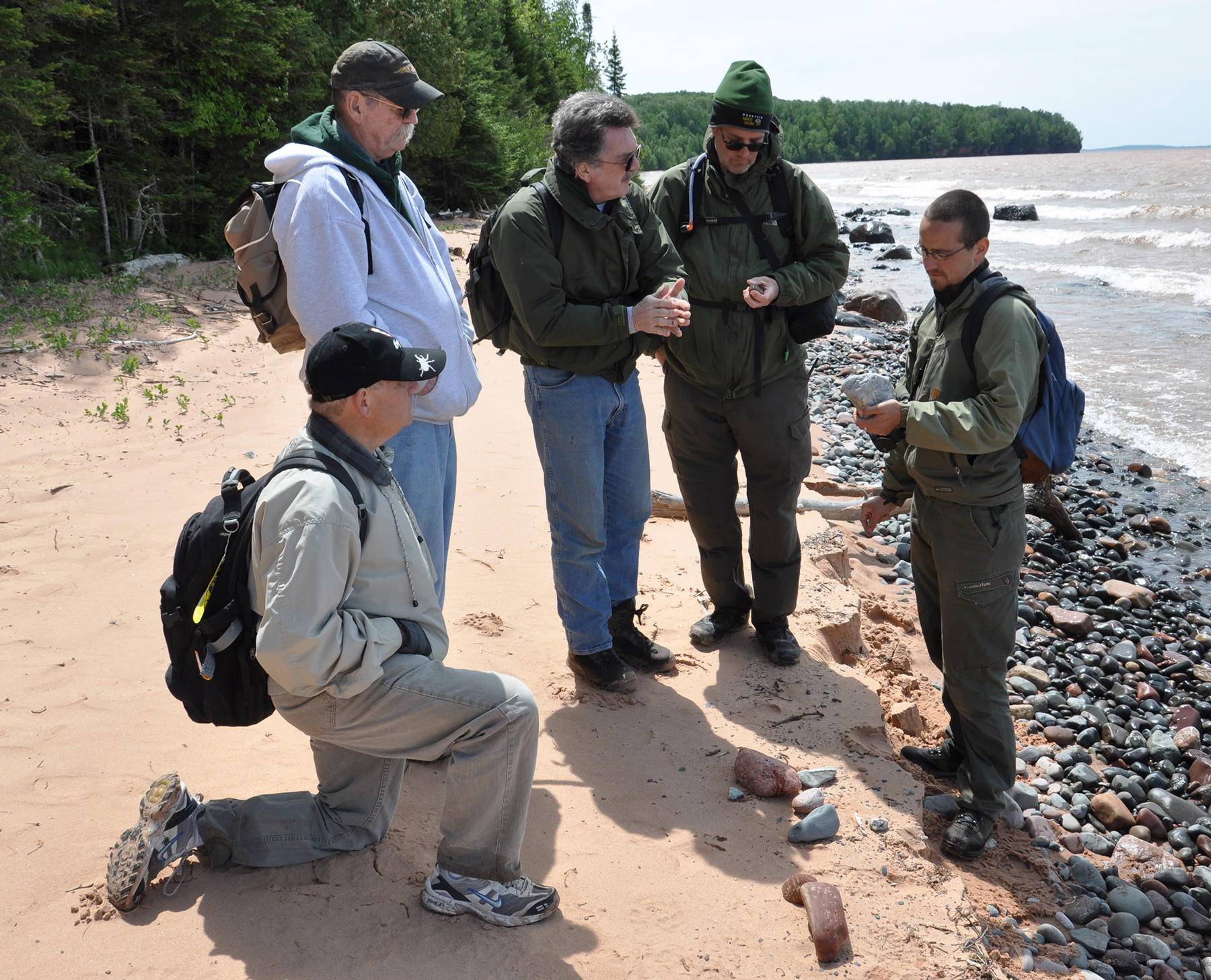Stu Whipple (center) with other park staff studying the rocks at Mawikwe Bay