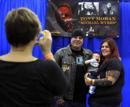 """Amber Rupp and her 3-month-old son Spencer, get their photo taken with actor Tony Moran, who played Michael Myers in the 1978 horror classic Halloween, Sunday during the Immersed in Ink Tattoo arts and Horror Festival at the Pensacola Interstate Fairgrounds"" -- Pensacola News Journal photo by John Blackie/jblackie@pnj.com"