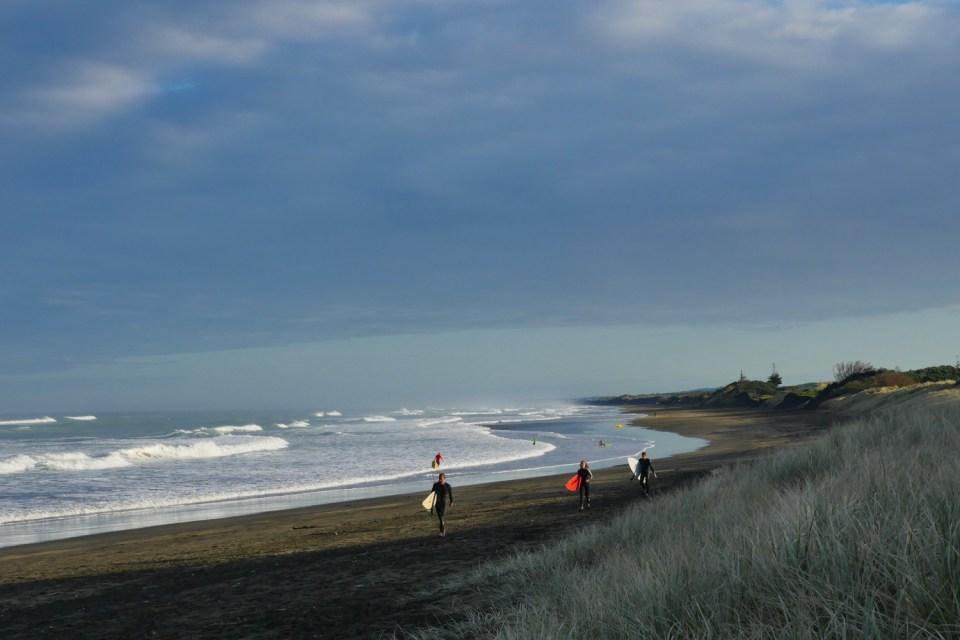 surfers at Muriwai beach