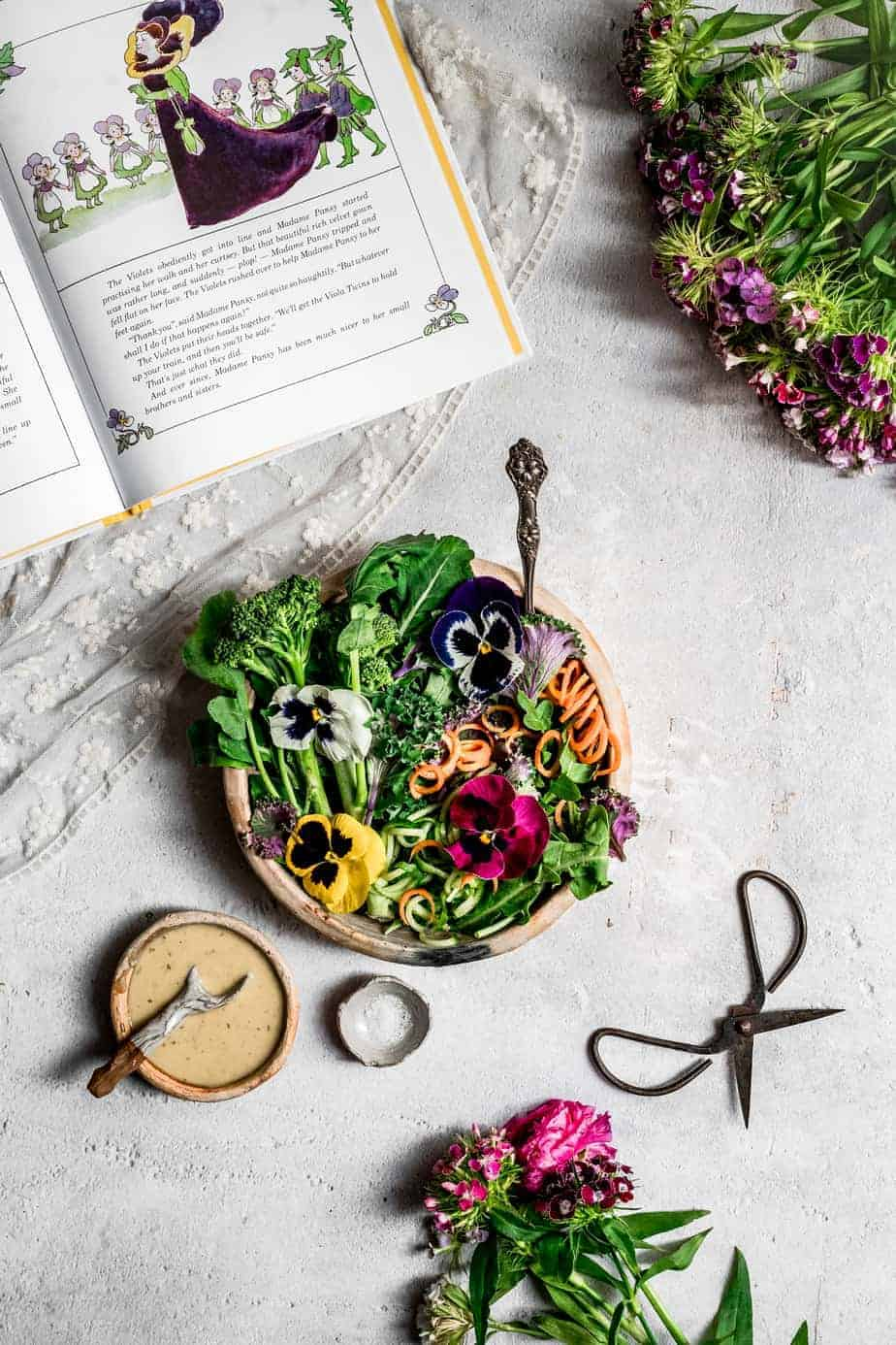 an overhead image of a rustic clay bowl with vibrant greens, spiralized caters and colorful edible pansies in white, yellow, pink and purple - with a homemade salad dressing