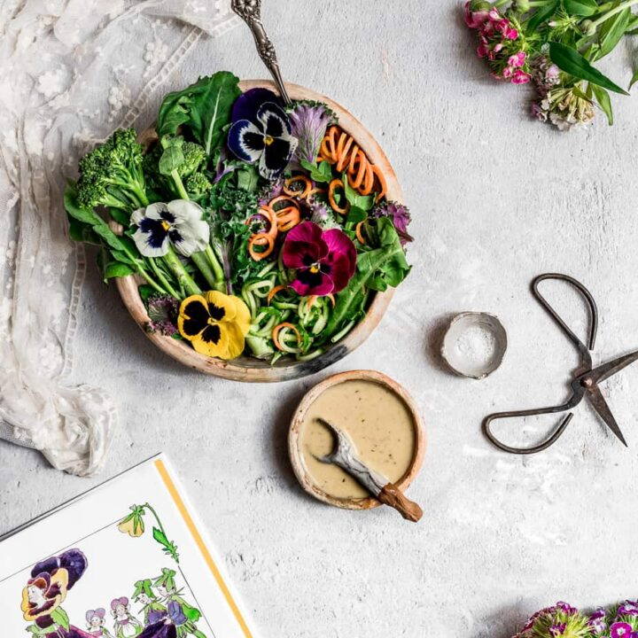 a rustic clay bowl with vibrant greens, spiralized caters and colorful edible pansies in white, yellow, pink and purple - with a homemade salad dressing