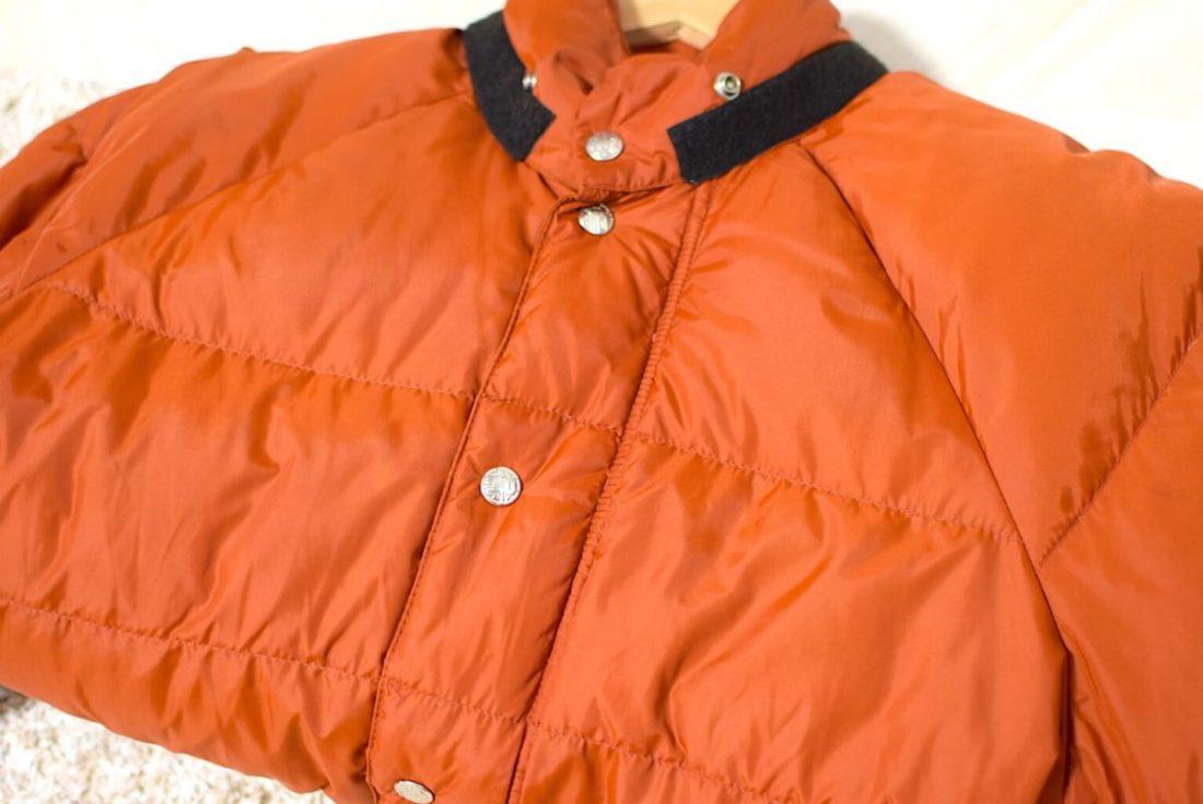 オレンジ色のREIのダウンジャケット