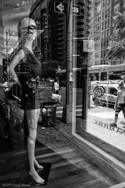 A mannequin caught in a world of confusing reflection on 86th street and Third Avenue in New York City.