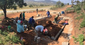 Community members begin building the house foundation