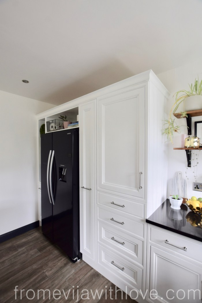 kitchen cabinets and black American style fridge freezer