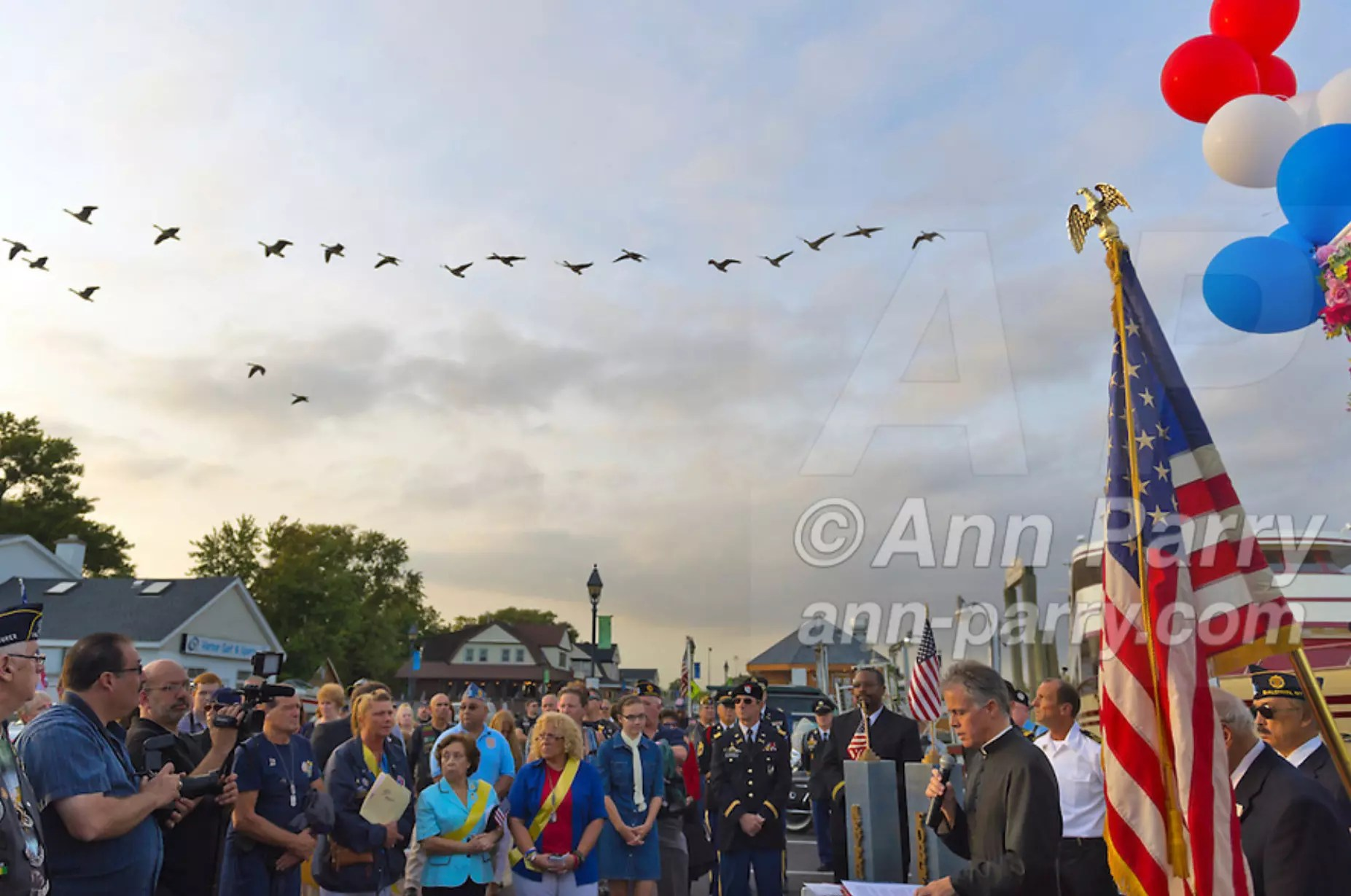Freeport, NY, USA. Sept. 10, 2014. A flock of birds flies overhead as pastor speaks at a dockside remembrance ceremony in honor of victims of the terrorist attacks of September 11 2001, at the boat Miss Freeport V, on Freeport's Nautical Mile. Further ceremonies were held on board the vessel, which sailed from the Woodcleft Canal on the South Shore of Long Island, on the eve of the 13th Anniversary of the 9/11 attacks.