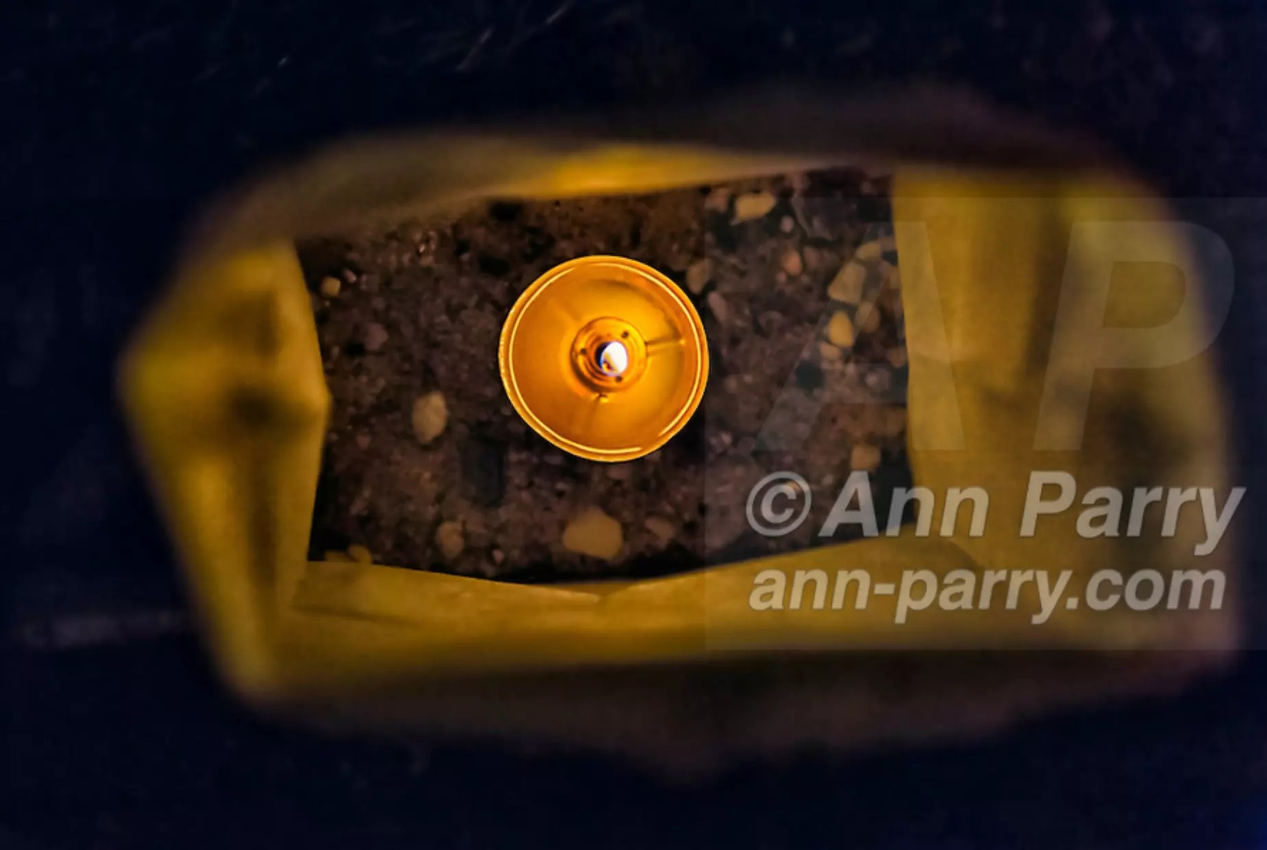 Merrick, NY, USA. Sept. 11, 2012. Lit tea candle is seen Inside one of 500 Luminary Bags distributed among the 215 Wenshaw Park homes on 11th Anniversary of 9/11, by Wenshaw Park Civic Association, Long Island, with over $500 already raised for Twin Towers Orphan Fund. Tea candle in each bag will self-extinguish overnight, and volunteers will collect the bags on 9/12.
