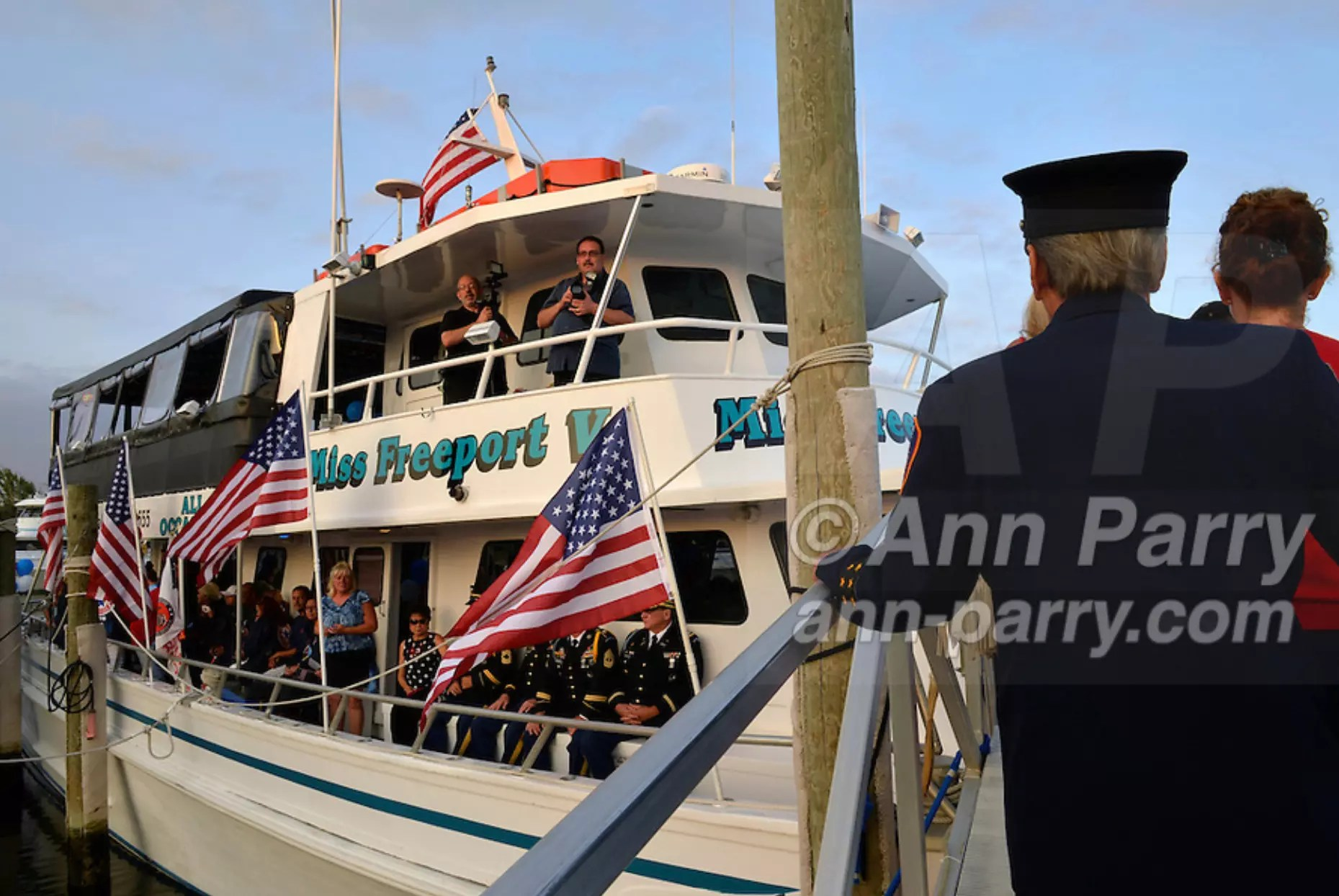 Freeport, NY, USA. Sept. 10, 2014. After a dockside remembrance ceremony in honor of victims of the terrorist attacks of September 11 2001, passengers walk up the gangplank to board the boat Miss Freeport V, which sailed from the Woodcleft Canal on Freeport's Nautical Mile on Long Island, on the eve of the 13th Anniversary of the 9/11 attacks. Further ceremonies were held on the boat.