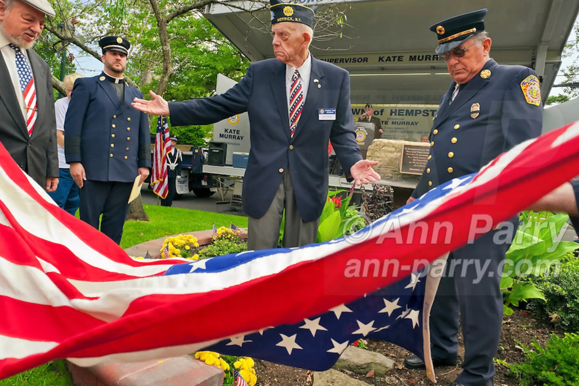 Merrick, NY, USA. Sept. 11, 2011. Removing American Flag to reveal monument made with steel from World Trade Center, at Merrick Post #1282 American Legion Tenth Anniversary of 9/11 event are, L-R, Rabbi Paul Kirchner, Father Eric Fasano, Adjutant Robert Tom Riordan PCC,; and North Merrick Fire Dept. Ex. Chief Henry Hinrichs, at Merrick Veterans Memorial Park.