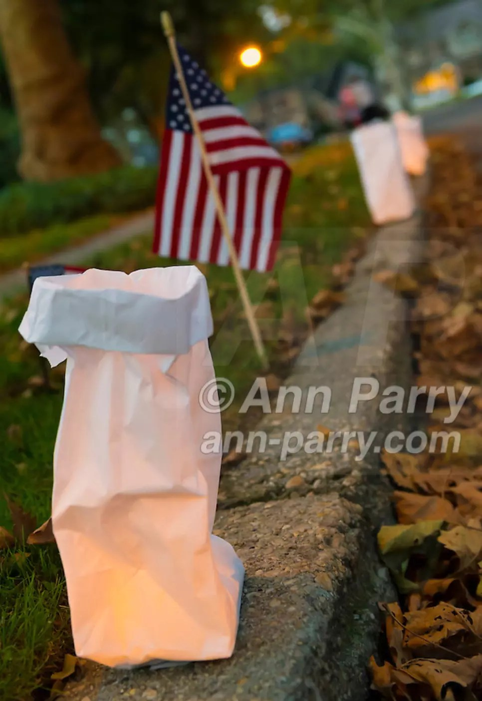 Merrick, NY, USA. Sept. 11, 2012. 500 Luminary Bags are distributed among the 215 Wenshaw Park homes on 11th Anniversary of 9/11, by Wenshaw Park Civic Association, with over $500 already raised for Twin Towers Orphan Fund. The tea candle in each bag will self-extinguish overnight, & volunteers will collect bags 9/12.