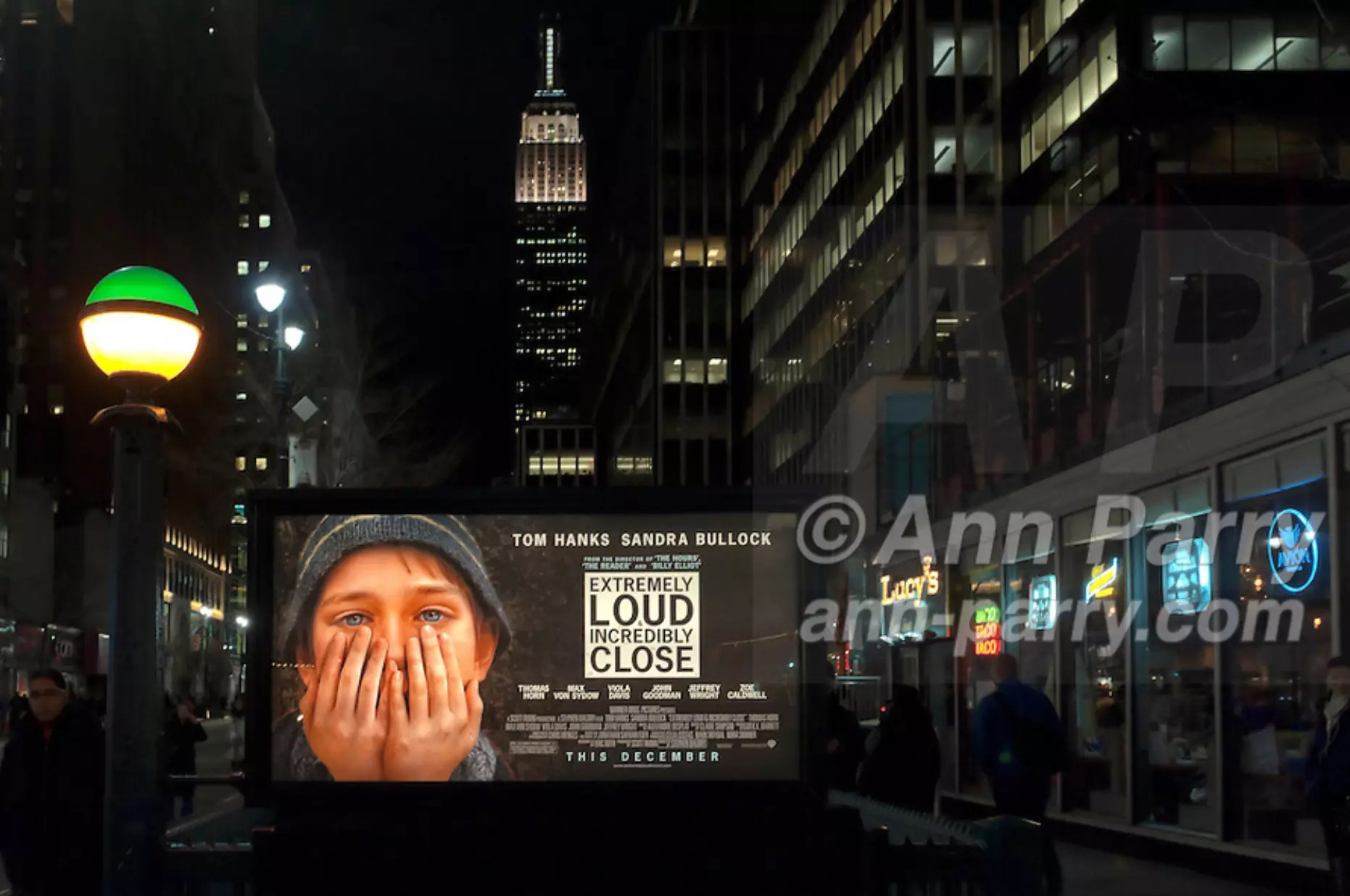 "Manhattan, NY, USA - January 9, 2012: Movie poster ""Extremely Loud & Incredibly Close"" hangs illuminated at night over Penn Station subway entrance with Empire State Building in background. Fictional movie is set at time of 9/11 terrorist attacks on Twin Towers in NYC. Green and yellow lit globe on post is at stairwell entrance to MTA (Metropolitan Transit Authority) 34 St. Penn Station subway station."