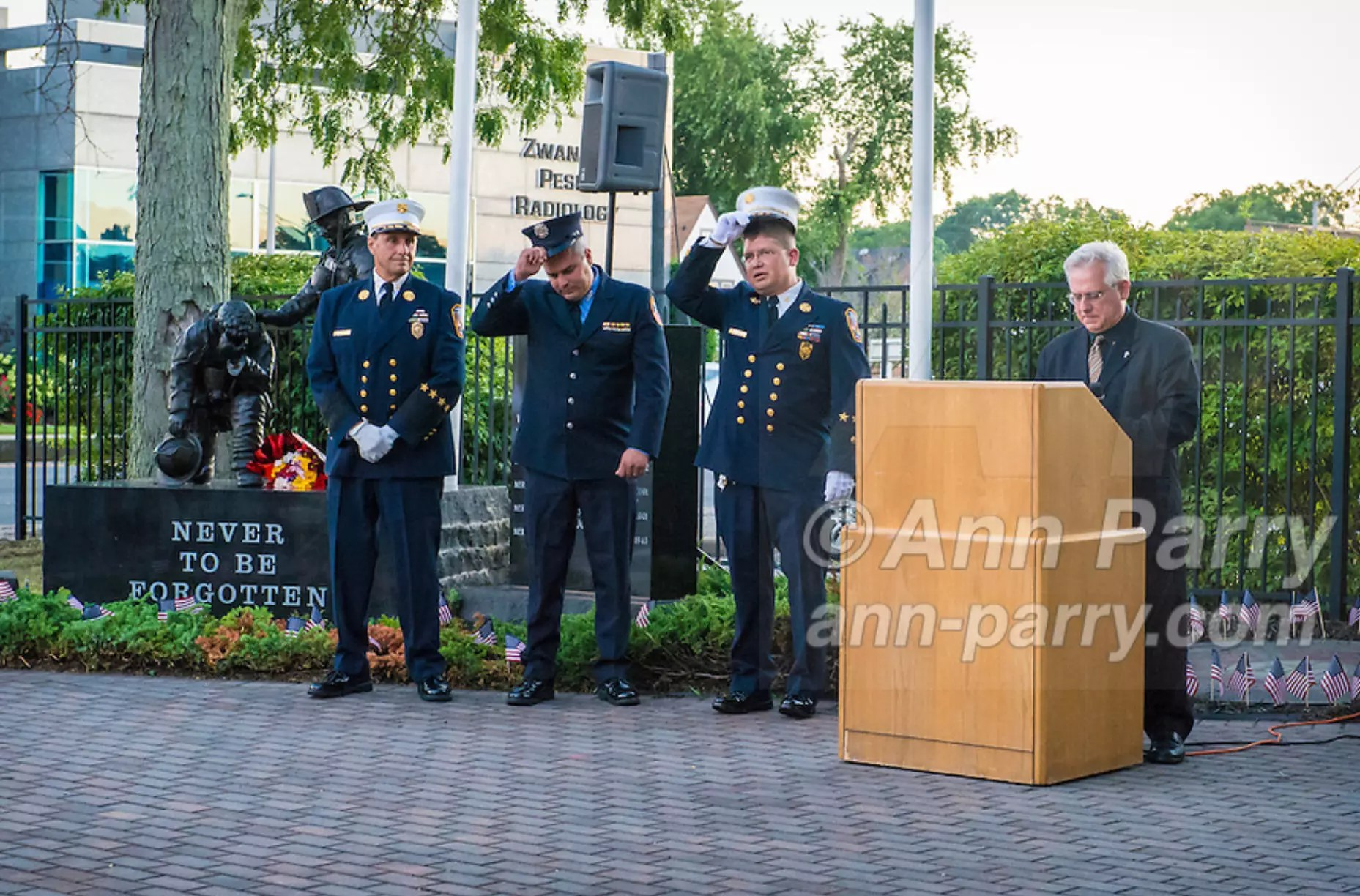 Merrick, NY, USA. 11th Sept. 2015. At podium, Deacon JOE ZUBROVICH, of Curé of Ars Roman Catholic Church in Merrick, begins invocation as 3 Merrick and NYC firefigthters, next to 9/11 statue momument, start to remove their dress uniform white caps during Merrick Memorial Ceremony for Merrick volunteer firefighters and residents who died due to 9/11 terrorist attack at NYC Twin Towers. Ex-Chief Ronnie E. Gies, of Merrick F.D. and FDNY Squad 288, and Ex-Captain Brian E. Sweeney, of Merrick F.D. and FDNY Rescue 1, died responding to the attacks on September 11, 2001.