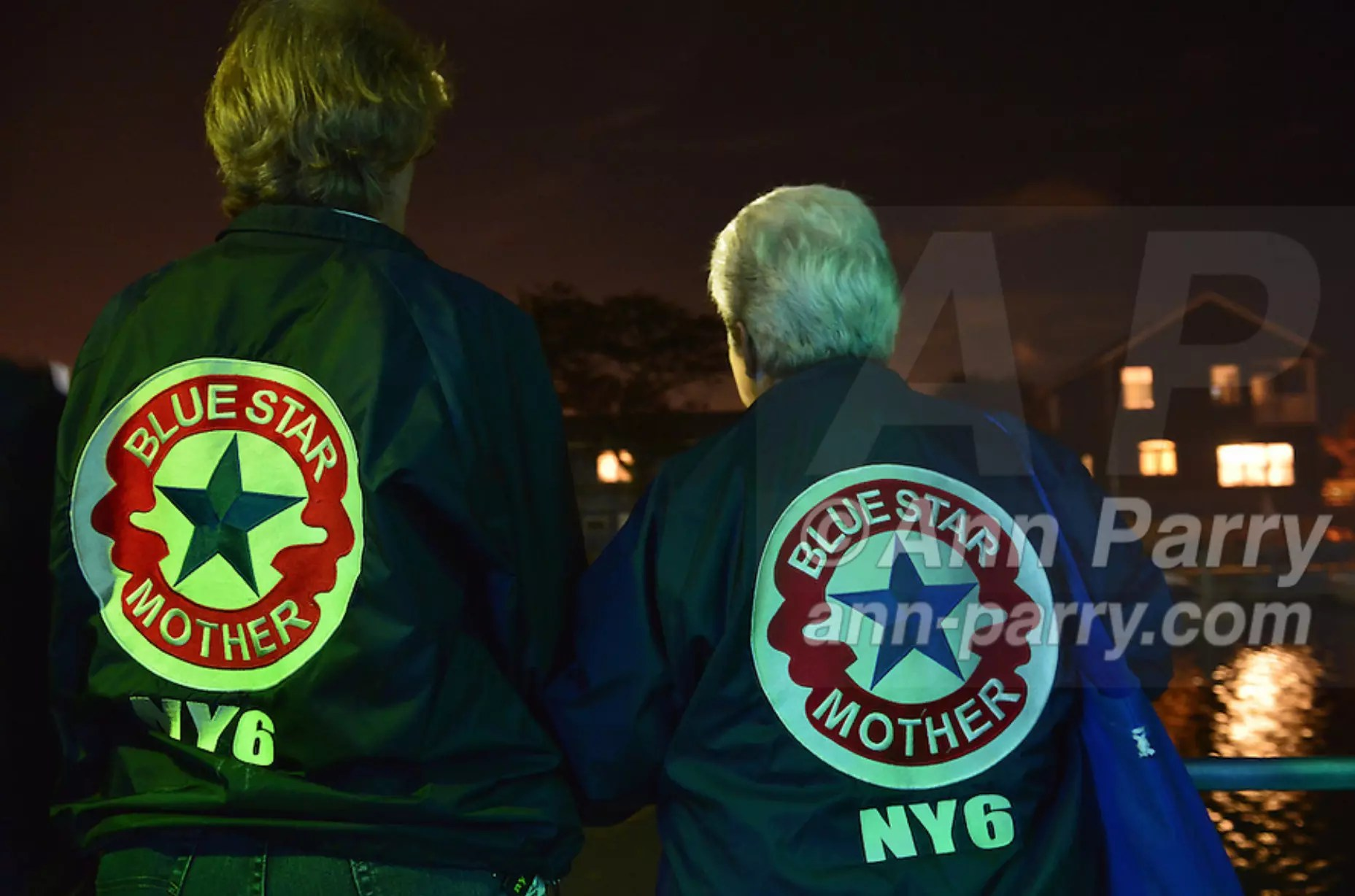 Freeport, NY, USA. Sept. 10, 2014. Two Blue Star Mothers of America members look at the shimmering night lights from houses along the canal while sailing on board the boat Miss Freeport V, which set sail from the Woodcleft Canal of the Freeport Nautical Mile after a dockside remembrance ceremony in honor of victims of the terrorist attacks of September 11 2001, on the eve of the 13th anniversary of the 9/11 attacks. On the back of each jacket is NY6, for the Long Island Blue Star Moms Chapter. Non-political Blue Star Mothers of America gives support for mothers with sons or daughters who are, or were, actively serving in the war.