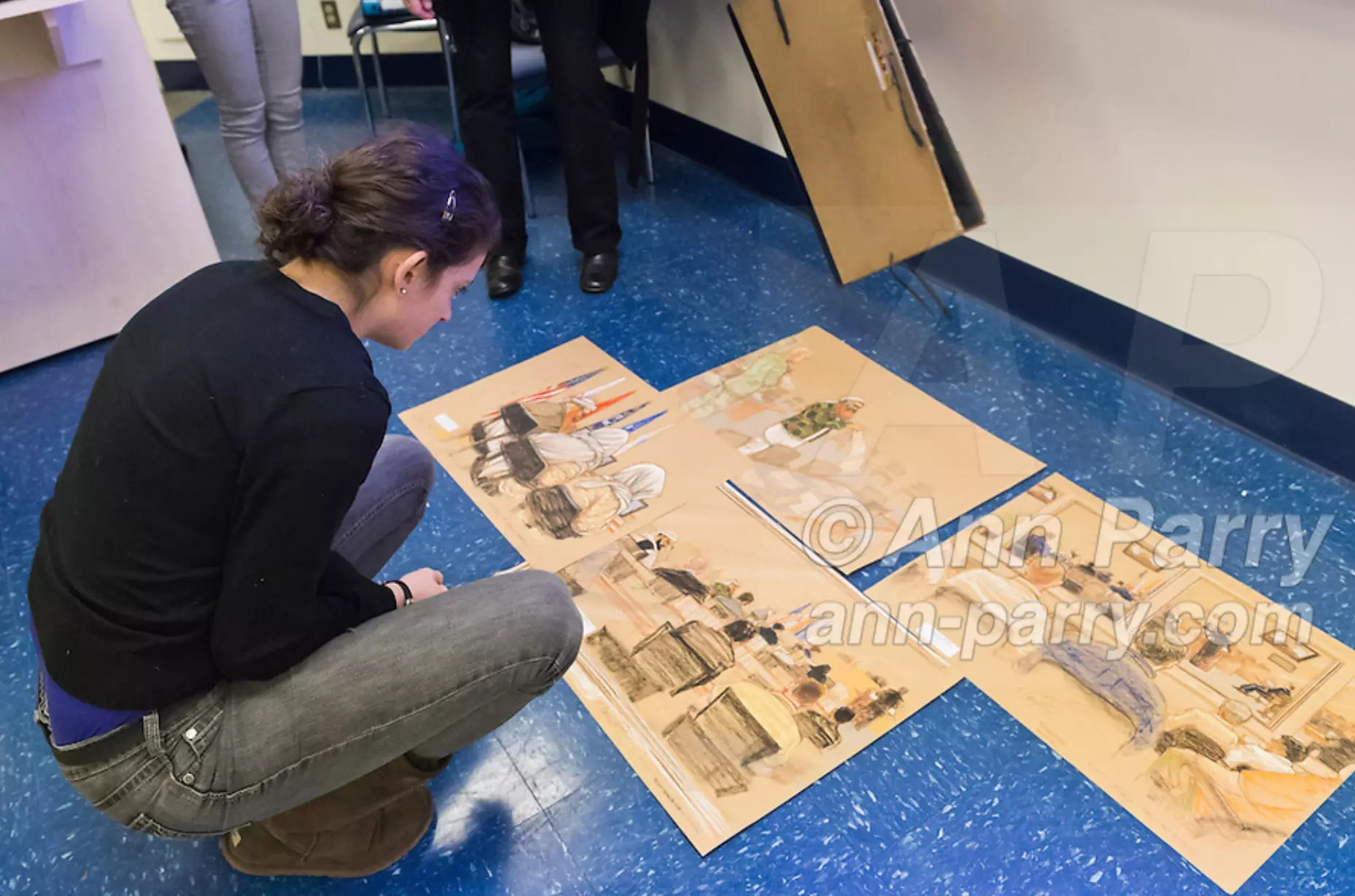 "Hempstead, NY, U.S. 12th Nov., 2013. Janet Hamlin, at back in black pants, a courtroom artist covering the military tribunals at Guantanamo Bay since 2006, shows her charcoal drawings and discusses her work at Hofstra University. A student is looking at sketches displayed on floor. Much of the time she was the only journalist providing a visual record of the events at the United States naval base in Cuba, and her new book ""Sketching Guantanomo"" is a collection of her images."