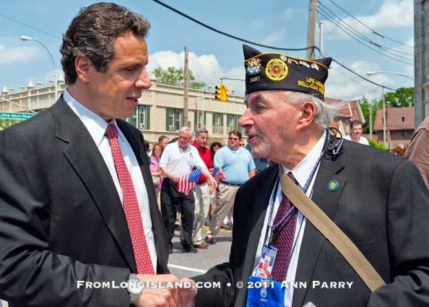 MAY 30, 2011 - Little Neck, New York, U.S. - NY Gov. ANDREW CUOMO stops to speak and shake hands with MARK KOPPELMAN, a U.S. Army veteran wearing US Press Corp Photographer Pass, of Oakland Gardens, during Little Neck-Douglaston Memorial Day Parade, on Northern Boulevard on May 30, 2011. (© 2011 Ann Parry)