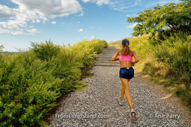 South Merrick, New York, USA. Woman is running uphill on Norman J Levy Park and Preserve Trail, on south shore of Long Island. (© 2014 Ann Parry, annparry.com)
