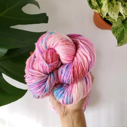 a hand holding up a skein of 'Unicorn Rave' with plants showing in the background