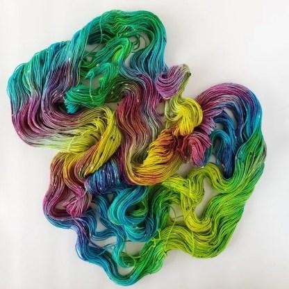 hand-dyed skein of yarn in the colorway 'Aquarela' on a tweed yarn base