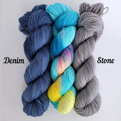 3 skeins of yarn showing the combination options for the shawl kits, 'Denim', 'Blue Lagoon' and 'Stone'
