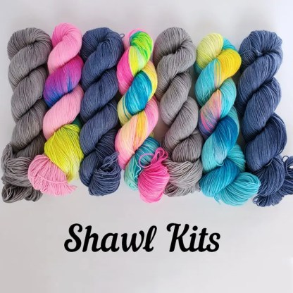 multiple skeins of yarn laid side by side in the center of the frame, alternating between solid colorways and rainbow colorways, to give an idea of the different colorway combinations available. There's black text in the bottom that reads 'Shawl Kits'