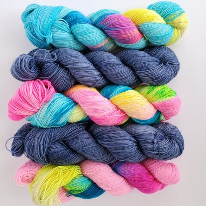 5 skeins of yarn laid top to bottom, 'Blue Lagoon', 'Sour Candy' and '90s kid' are alternated by 'Denim' colorway