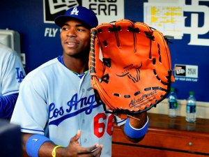 June 20, 2013; San Diego, CA, USA; Los Angeles Dodgers right fielder Yasiel Puig (66) with a giant glove in the dugout prior to the game against the San Diego Padres at Petco Park. Mandatory Credit: Christopher Hanewinckel-USA TODAY Sports