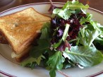 Perfectly toasted meatloaf sandwich on perfect slices of fresh pain de mie and a side salad of baby greens