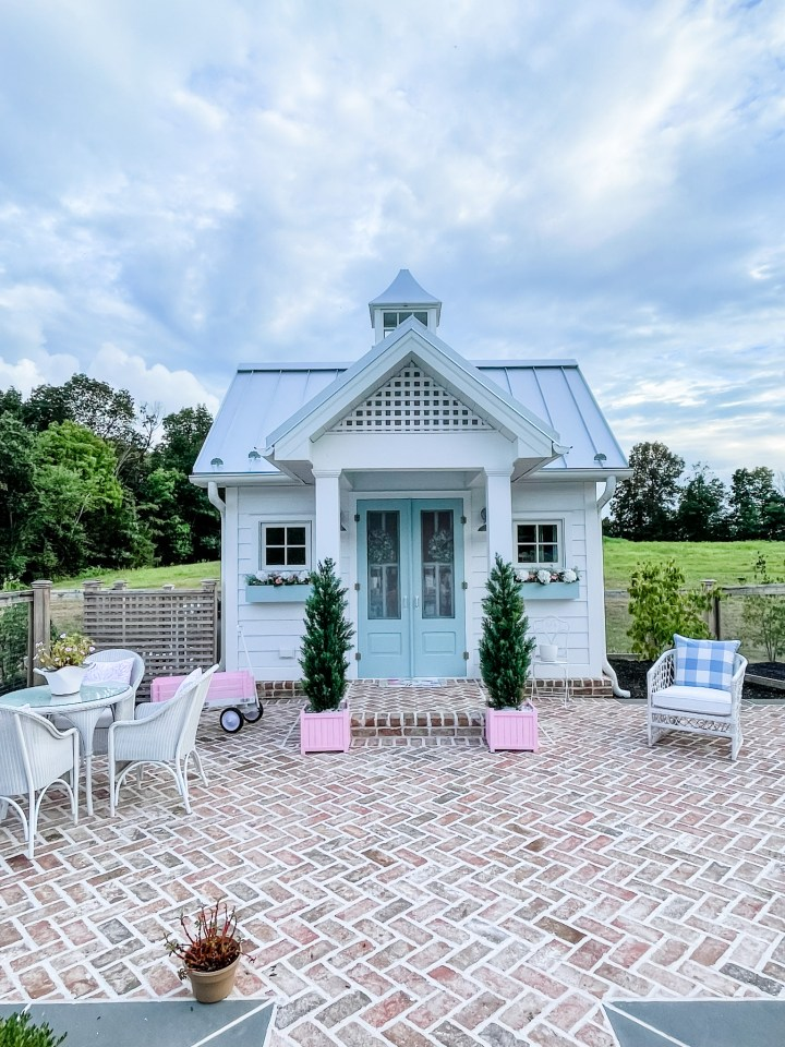 White pool house with metal roof and blue doors