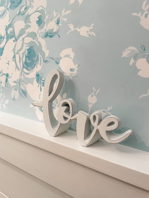 wallpaper in a powder room with a white love sign