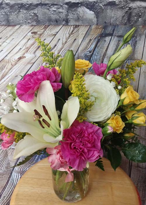 Lilies carnations spray roses and ranunculus blooms jar Bouquet