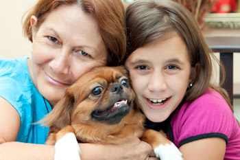 mother-and-daughter-hugging-dog-350