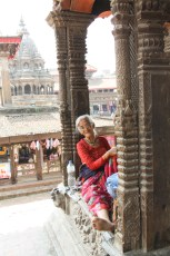 A granny relaxes in a temple niche, Patan