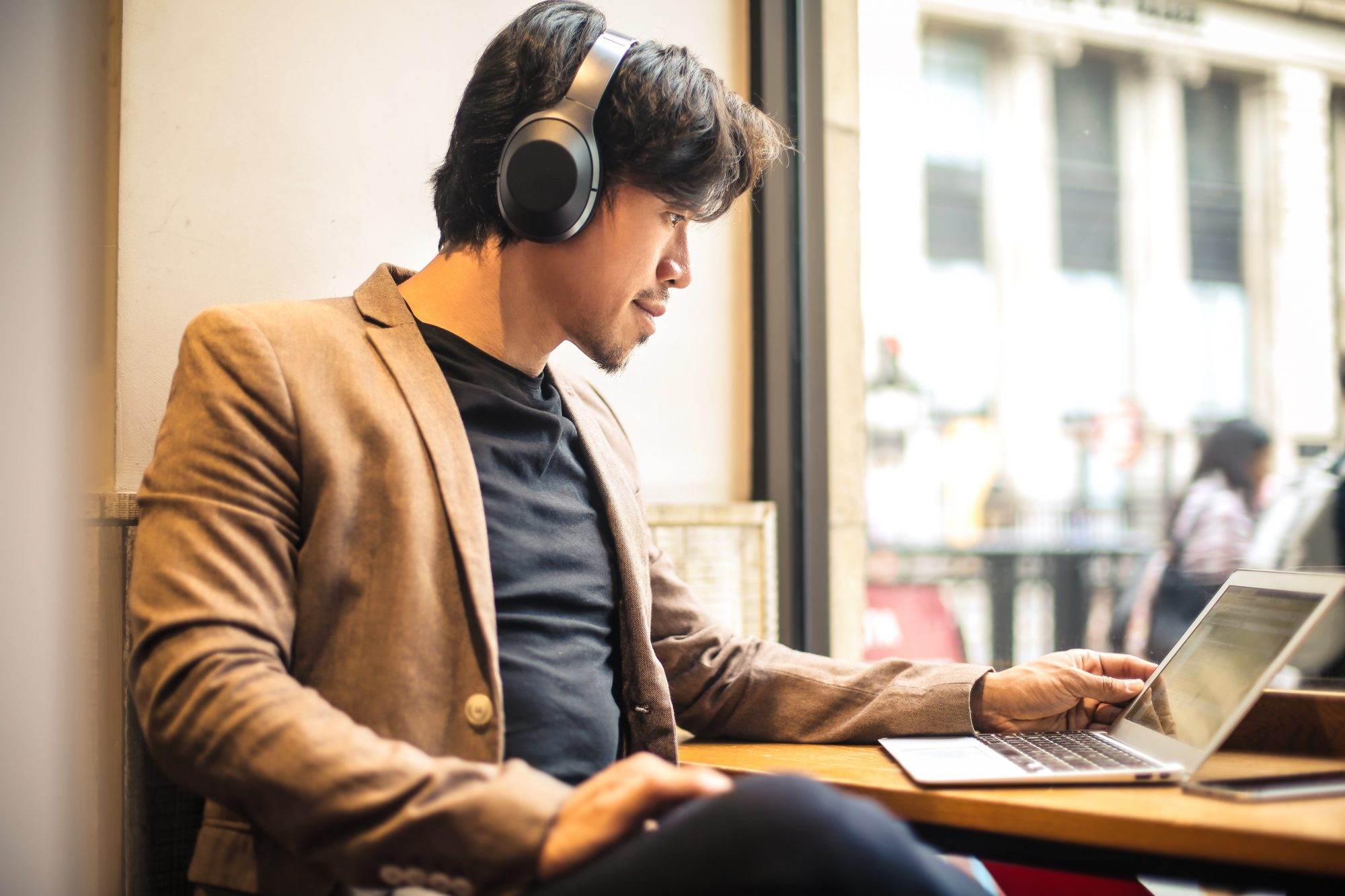 Guy working with his laptop, listening to something