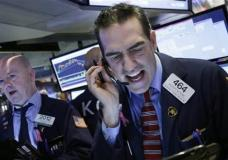 Stock trader Gregory Rowe works at the New York Stock Exchange, Friday, Jan. 15, 2016. (AP Photo/Mark Lennihan)