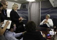 U.S. Secretary of State John Kerry, right, speaks to journalists about his negotiations with Iran upon his arrival from Vienna at Joint Base Andrews in Washington Sunday, Jan. 17, 2016. Four Americans and seven Iranians got tickets to freedom in a prisoner swap playing out alongside the kick-start of an accord lifting heavy international sanctions on Iran in return for its agreement to pull back its nuclear program. A fifth American was released separately. (Kevin Lamarque/Pool Photo via AP)