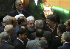 """Iranian President Hassan Rouhani, center, is surrounded by lawmakers as he leaves the parliament after presenting draft of the country's next year budget and sixth development plan in Tehran, Iran, Sunday, Jan. 17, 2016. Rouhani said Sunday that the official implementation of the landmark deal reached between Tehran and six world powers has satisfied all parties except radical extremists. Rouhani said the deal has """"opened new windows for engagement with the world."""" (AP Photo/Vahid Salemi)"""