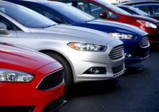 This Thursday, Nov. 19, 2015, photo, shows a row of new 2015 Ford Fusions on the sales lot at Butler County Ford in Butler, Pa. Automakers report December and full-year sales Tuesday, Jan. 5, 2016. (AP Photo/Keith Srakocic)