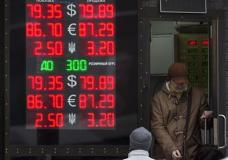 A man leaves an exchange office as a screen shows the currency exchange rates of the Russian ruble, U.S. dollar, euro and Ukrainian Hrivna in Moscow, Russia, Wednesday, Jan. 20, 2016. The Russian ruble slid to a record low against the dollar Wednesday under pressure from the low oil price, beating a mark set when the currency crashed in value in December 2014 before stabilizing. (AP Photo/Alexander Zemlianichenko)