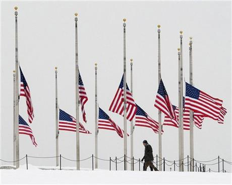 A vistor to the Washington Monument walks past flags flying a half-staff in honor of Supreme Court Justice Antonin Scalia on a wintry Presidents Day holiday in Washington, Monday, Feb, 15, 2016. (AP Photo/J. David Ake)