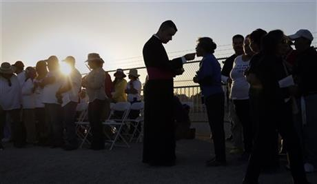 Migrants watching Pope Francis' Mass in Juarez, Mexico, from a levee along the banks of the Rio Grande in El Paso, Texas, take part in Communion, Wednesday, Feb. 17, 2016. (AP Photo/Eric Gay)