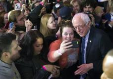 Democratic presidential candidate Sen. Bernie Sanders, I-Vt., poses for photos during a caucus night rally on Monday, Feb. 1, 2016, in Des Moines, Iowa. (AP Photo/Evan Vucci)