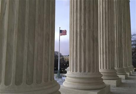 The U.S. flag blows in the wind, seen through columns at the Supreme Court building in Washington on Saturday, Feb. 13, 2016. On Saturday, Feb. 13, 2016, the U.S. Marshals Service confirmed that Scalia has died at the age of 79. (AP Photo/Jon Elswick)