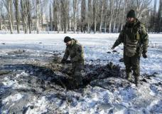 A Ukrainian soldier inspects a crater left by an explosion in Avdiivka, Ukraine, Tuesday, Jan. 31, 2017. Fighting between government troops and Russia-backed separatist rebels in eastern Ukraine escalated on Tuesday, killing at least eight people late Monday and early Tuesday, injuring dozens and briefly trapping more than 200 coal miners underground, the warring sides reported.(AP Photo/Inna Varenytsia