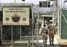 """FILE - In this June 27, 2006 file photo, reviewed by a US Department of Defense official, US military guards walk within Camp Delta military-run prison, at the Guantanamo Bay US Naval Base, Cuba. A draft executive order shows President Donald Trump asking for a review of America's methods for interrogation terror suspects and whether the U.S. should reopen CIA-run """"black site"""" prisons outside the U.S. (AP Photo/Brennan Linsley, file)"""