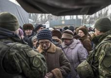 Local residents queue to receive aid at a humanitarian aid center in Avdiivka, eastern Ukraine, Wednesday, Feb. 1, 2017. Freezing residents of an eastern Ukraine town battered by an upsurge in fighting between government troops and Russia-backed rebels flocked to a humanitarian aid center Wednesday to receive food and warm up. (AP Photo/Evgeniy Maloletka)