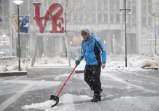 A man clears snow from Dilworth Park during a winter storm in Philadelphia, Thursday, Feb. 9, 2017. A powerful, fast-moving storm swept through the northeastern U.S. Thursday, making for a slippery morning commute and leaving some residents bracing for blizzard conditions. (AP Photo/Matt Rourke)